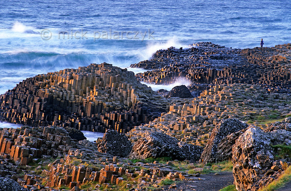 [BRITAIN.IRELANDNORTH 21.851] 'Fin's bridge.'  	The basaltic rock columns of Giant's Causeway are battered by the Atlantic Ocean. According to myth the Causeway was built as a bridge to Scotland by the giant Finn, who wanted to test his strength against his Scottish rival Fingal. Photo Mick Palarczyk.