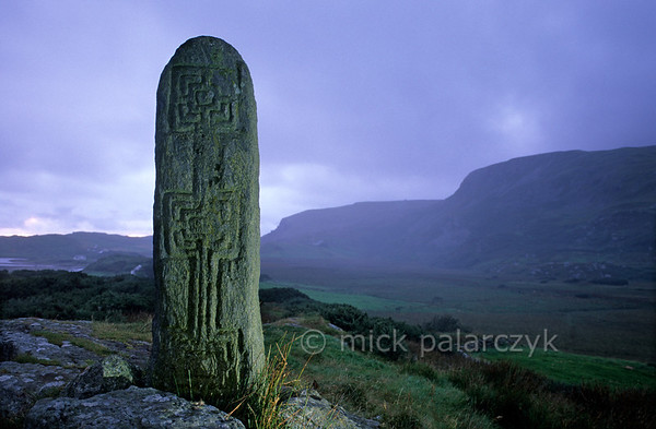 [IRELAND.DONEGAL 21.780] 'Labyrinth cross.'  	This 'Turas Cholmcille' at Glencolumbkille has been erected as a prehistoric menhir and was christianized in the 6th century by St. Columb who inscribed a labyrinth-like cross in it. Photo Mick Palarczyk.