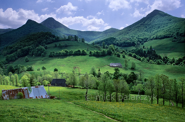 [FRANCE.AUVERGNE 28899] 'The heart of the Cantal volcano.'  From the Vallée de Mandailles near the village of Rudez you have a fine view of a green landscape with old barns and the higher summits at the centre of the Cantal. To the left sits the Puy Griou, a volcanic plug. Geologists think that this was once the central duct of the giant Cantal volcano, the largest stratovolcano of Europe. Lava coagulated in the duct after which the surrounding material eroded away and the more resistant lava plug remained. Photo Mick Palarczyk.