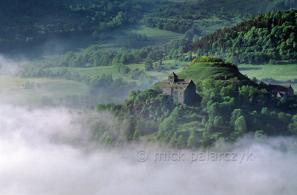 [FRANCE.AUVERGNE 28885] 'Church of Albepierre-Bredons.'  South of Murat, in the eastern Cantal, the fortified church of Albepierre-Bredons emerges from the morning fog. The building, which dates from the 11th century, is the only remnant of a Benedictine priory. Photo Mick Palarczyk.