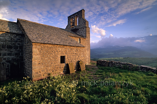 [FRANCE.AUVERGNE 28886] 'Chapel of Chastel-sur-Murat.'  The 12th century St. Antoine Chapel sits atop a basaltic hill near the village of Chastel-sur-Murat in the eastern Cantal. From its overgrown cemetery there is a fine view of the Plomp du Cantal, the highest mountain of the region. Photo Mick Palarczyk.
