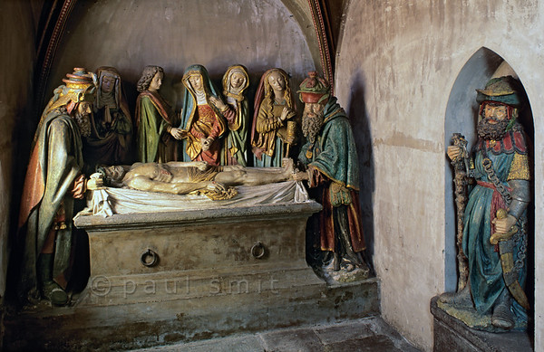 [FRANCE.AUVERGNE 28932] 'Entombment of Christ in Salers.'  The St. Matthieu church of Salers in the western Cantal has a splendid late medieval stone statue group depicting the interment of Christ. It is a work of the Burgundian school but also shows Flemish influences. In the centre Mary is consoled by St. John, with Mary Magdalene more to the right (with free flowing hair). The two extremities are occupied by the old men Nicodemus and Joseph of Arimathea. In the alcove to the right is the roman guard of the grave. Photo Paul Smit .