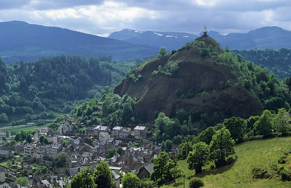 [FRANCE.AUVERGNE 28887] 'Murat.'  Murat, in the eastern Cantal, has a grey appearance with its slate roofs and basalt rock walls. The hill behind it (topped by a white statue of Mary) also consists of basalt and on the steepest slopes hexagonal basalt columns can be recognized. We are looking at a socalled volcanic plug here: lava coagulated in the duct of an active volcano after which the cone eroded away and the more resistant lava plug remained. Photo Paul Smit.