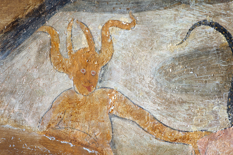 [FRANCE.ALPSSOUTH 29076] 'Devils in Roure (detail).'  The lower left wall in the St. Sebastian chapel of Roure, a village 45 km north of Nice, showsa group of devils who are leading a priest and a naked woman to hell. The scene echoes a historic village scandal from 1427 in which Pierre Blanqui, priest of Roure, committed adultery with Delphine, the lawful wife of Jean Bovis.The fresco was executed in 1510 by Andrea de Cella, one of the so-called 'peintres primitifs niçois' (primitive painters of Nice). Photo Mick Palarczyk.