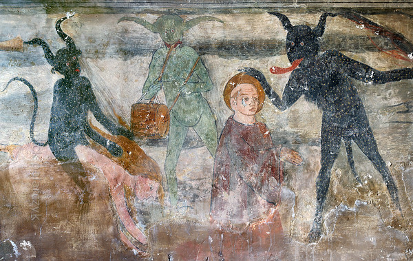 [FRANCE.ALPSSOUTH 29071] 'Devils in Roure.'  	The lower left wall in the St. Sebastian chapel of Roure, a village 45 km north of Nice, shows a group of devils who are leading a priest and a naked woman to hell. The devil on the right is taking away the aureole of the cleric while the one on the left is riding the woman as a horseman. The painting echoes a historic village scandal from 1427 in which Pierre Blanqui, priest of Roure, committed adultery with Delphine, the lawful wife of Jean Bovis.The fresco was executed in 1510 by Andrea de Cella, one of the so-called 'peintres primitifs niçois' (primitive painters of Nice). Photo Mick Palarczyk.