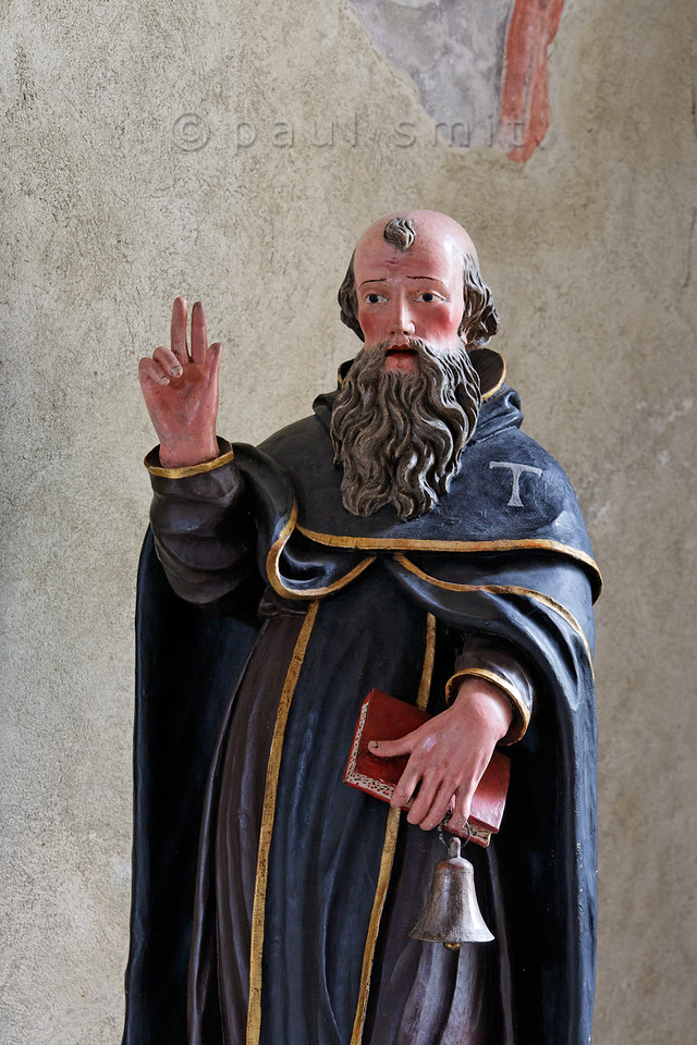 "[FRANCE.ALPSNORTH 10965] 'Saint Anthony.'  Saint Anthony (the Great) is shown as a monk in the Chapelle Saint Antoine in Bessans . That's because he is often called the father of all monks, because he was the first Christian eremite to attempt living in the Egyptian desert and not on the city outskirts as some ascetics had done before him. This inspired others to a monastic way of life. The bell and the letter T ('tau"") are his attributes.  In the Alps Saint Anthony is the patron saint of domesticated animals. Since Savoy has always been famous for its cheese and since the Col de Mont Cenis was one of the most important routes to Italy in those days, cattle farmers and the donkey drivers recognized Anthony as their best friend. Therefore nearly every village in the Haute Maurienne has its own St. Anthony chapel. Photo Paul Smit."