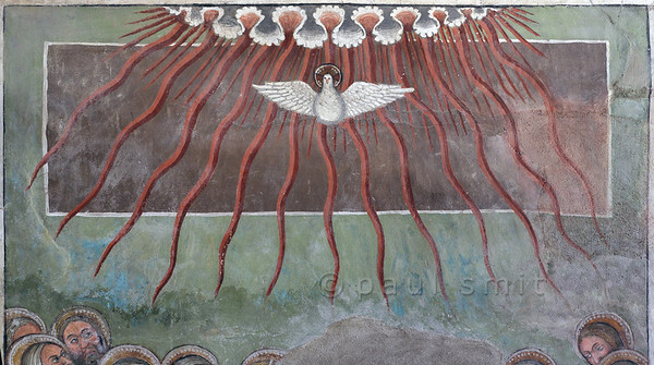[FRANCE.ALPSNORTH 10964] 'The Holy Spirit.'  The interior of the Chapelle Saint Antoine in Bessans is covered with frescoes, and a part of the exterior as well. With wonderful details, like this Holy Spirit, symbolized by a dove. At Pentecost it was outpoured over the apostles, associated with tongues of fire. Heaven, from where it comes, is symbolized by what looks like the edge of a curtain. The chapel and its frescoes date from the beginning of the 16th century. Photo Paul Smit.