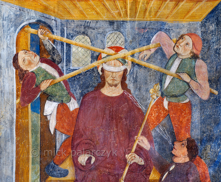 [FRANCE.ALPSSOUTH 29087] 'Derision of Christ.'  The ninth of twenty panels depicting the Passion of Christ in the Chapelle des Pénitents Blancs at La Tour shows the derision of a blindfolded Jesus (detail). He is spat at and two men use canes to press the crown of thorns on his head (the crown itself is not visible, though). The fresco was executed in 1492 on the chapel's right wall by Currand Bravesi and Guirard Nadal, two of the so-called 'peintres primitifs niçois' (primitive painters of Nice). La Tour sur Tinée is a village in the French Alps, 30 km north of Nice. Photo Mick Palarczyk.