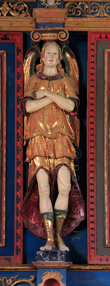 [FRANCE.ALPSNORTH 10979] 'Angel in flared pants.'  The Haute Maurienne is reknown for its art along the <i>Chemins du Baroque</i>, the Baroque Trail. Most of the angels seen in the local churches and chapels are putti, baby angels. But the Chapelle Saint Sébastien in Lanslevillard hosts two teenagers, of which this is one, in the role of a caryatid. He is wearing amazing flared pants and colourful toe-less boots. A real dandy! Photo Paul Smit.