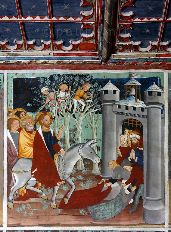 [FRANCE.ALPSNORTH 10973] 'Triumphal Entry into Jerusalem.'  Not only do the frescoes in the Chapelle Saint Sébastien in Lanslevillard reach an astonishing high artistic level, the colours have kept their original saturation as well. This most important work of art in the Haute Maurienne has been painted at the end of the 15th century by artists from Piemonte (now in Italy but then in the same country: Savoy). Its location may seem unexpected: a small village deep in the Alps. But the chapel is situated right at the start of the pass road over the Col du Mont Cenis, in those days one of the main connections between France and Italy.  The fresco shows the arrival of Jesus in Jerusalem on a donkey, which is celebrated within Christianity at Palm Sunday. That's because people laid down branches of palm trees (although the fresco shows different trees, better suited for the European onlookers). People laid down cloaks as well. A part of the painted, coffered ceiling can be seen above the fresco. Photo Paul Smit.