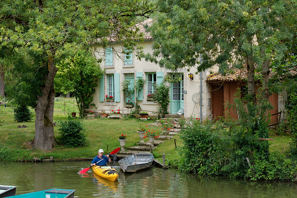 [FRANCE. ATLANTIC 30022] 'Kayaker near cottage in Arçais.'