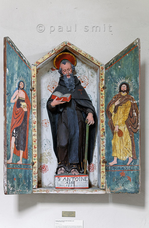 "[FRANCE.ALPSNORTH 10985] 'Saint Anthony.'  Saint Anthony (the Great) is shown as a monk in the Espace Baroque museum in Lanslebourg. That's because he is often called the father of all monks, because he was the first Christian eremite to attempt living in the Egyptian desert and not on the city outskirts as some ascetics had done before him. This inspired others to a monastic way of life. The bell and the letter T ('tau"") are his attributes.  In the Alps Saint Anthony is the patron saint of domesticated animals. Since Savoy has always been famous for its cheese and since the Col de Mont Cenis was one of the most important routes to Italy in those days, cattle farmers and the donkey drivers recognized Anthony as their best friend. Therefore nearly every village in the Haute Maurienne has its own St. Anthony chapel.  This statue, carved out of wood and painted, is made in 1629 by Jean Clappier. The box is painted by less talented village artists and shows John the Baptist and Matthew. Photo Paul Smit."