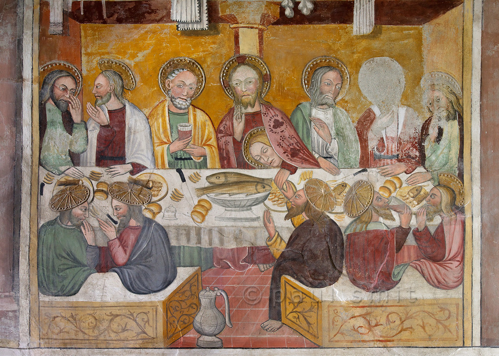 """[FRANCE.ALPSNORTH 10959] 'Last Supper.'  Two things hit the eye in this Last Supper fresco in the Chapelle de Saint Antoine in Bessans. First: the areoles. The apostles seen on the back seem to have hats of bolted gold! Second: the person in Christ's embrace. We know it should be St.  John the Evangelist, also known as the Disciple whom Jesus Loved. But we have all read Dan Brown's """"Da Vinci Code"""", and he concluded that this person is a woman: his lover!  The chapel and its frescoes date from the beginning of the 16th century. Photo Paul Smit."""