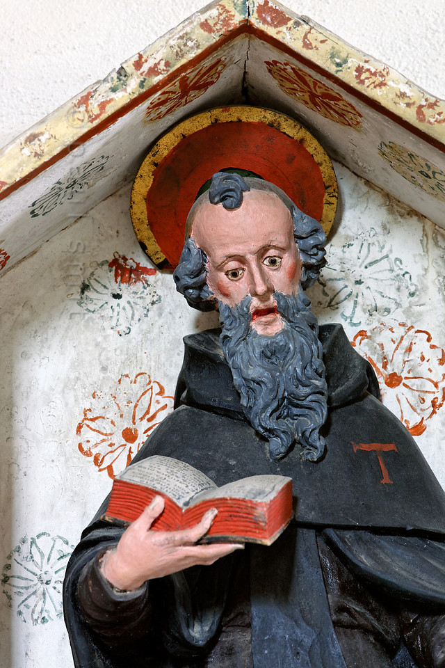 """[FRANCE.ALPSNORTH 10986] 'Saint Anthony.'  Saint Anthony (the Great) is shown as a monk in the Espace Baroque museum in Lanslebourg. That's because he is often called the father of all monks, because he was the first Christian eremite to attempt living in the Egyptian desert and not on the city outskirts as some ascetics had done before him. This inspired others to a monastic way of life. The bell and the letter T ('tau"""") are his attributes.  In the Alps Saint Anthony is the patron saint of domesticated animals. Since Savoy has always been famous for its cheese and since the Col de Mont Cenis was one of the most important routes to Italy in those days, cattle farmers and the donkey drivers recognized Anthony as their best friend. Therefore nearly every village in the Haute Maurienne has its own St. Anthony chapel.  This statue, carved out of wood and painted, is made in 1629 by Jean Clappier. Photo Paul Smit."""