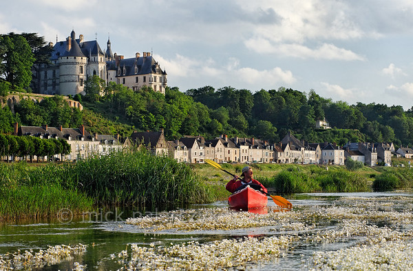 [FRANCE.LOIRE 10829] 'Chaumont's Castle seen from a paddler's perspective.'  The 15th century castle of Chaumont-sur-Loire looks down on a paddler navigating the loire between Blois and Amboise. Locally the river is covered by large patches of flowering River Water-crowfoot (Ranunculus fluitans; NL: Vlottende waterranonkel). Rooted in the riverbed, it produces strands of up to 6 meters in length, that are stretched out in the direction of the current. Photo Mick Palarczyk.