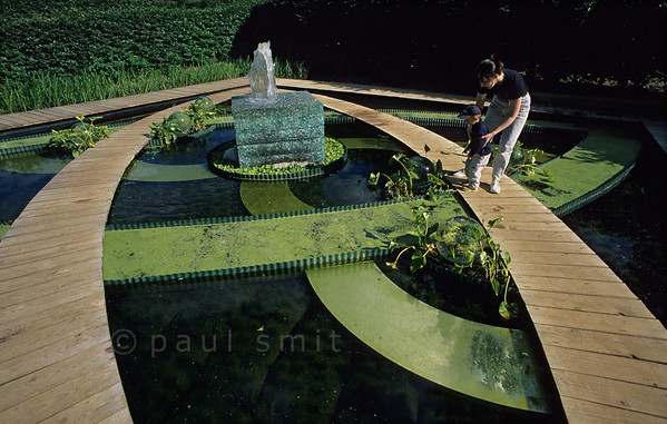 [FRANCE.LOIRE 10831] 'Geometrical garden at Chaumont.'  	At the International Garden Festival at the castle of Chaumont-sur-Loire a boy and his mother investigate a watery garden that is inspired by the curved hedges in the geometrical gardens of Villandry Castle. Photo Paul Smit.