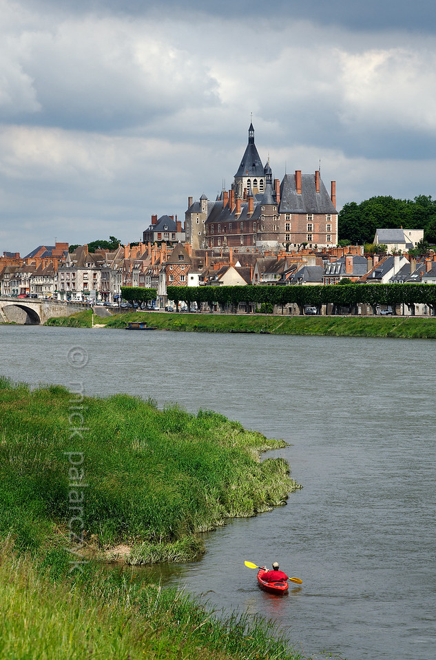 [FRANCE.LOIRE 10786] 'Kayaker on the Loire at Gien.'  Advancing towards Gien by kayak on the Loire one is struck by the brick-built Castle of Anne de Beaujeu (ca. 1500) which dominates the town. Photo Mick Palarczyk.