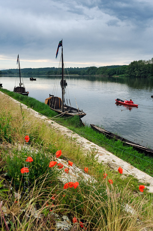 [FRANCE.LOIRE 10845] 'Loire quay with poppies at Bréhémont.'  	The Loire quay at Bréhémont with its moored traditional flatboats ('chalands') is an interesting spot to investigate for kayakers. Photo Mick Palarczyk.