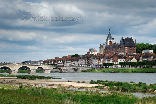 [FRANCE.LOIRE 10784] 'Kayaker on the Loire at Gien.'  The brick-built Castle of Anne de Beaujeu (ca. 1500) dominates the town of Gien. Its Loire bridge originally dates from the Middle Ages but was reconstructed in the 18th century. Photo Mick Palarczyk.