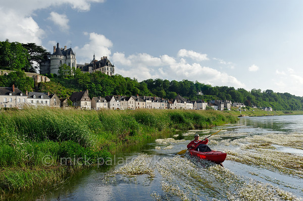 [FRANCE.LOIRE 10825] 'Chaumont's Castle seen from a paddler's perspective.'  The 15th century castle of Chaumont-sur-Loire looks down on a paddler navigating the loire between Blois and Amboise. Locally the river is covered by large patches of flowering River Water-crowfoot (Ranunculus fluitans; NL: Vlottende waterranonkel). Rooted in the riverbed, it produces strands of up to 6 meters in length, that are stretched out in the direction of the current. Photo Mick Palarczyk.