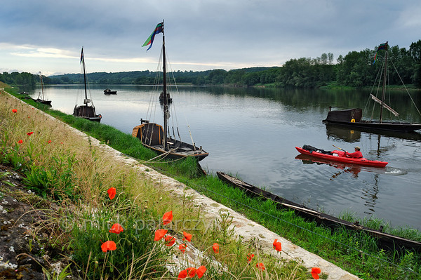 [FRANCE.LOIRE 10847] 'Loire quay with poppies at Bréhémont.'  	The Loire quay at Bréhémont with its moored traditional flatboats ('chalands') is an interesting spot to investigate for kayakers. Photo Mick Palarczyk.