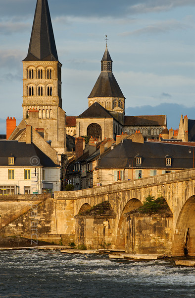[FRANCE.BOURGOGNE 10775] 'Bridge of La Charité-sur-Loire.'  A heron is prowling for fish in the turbulent waters downstream of the medieval bridge in La Charité-sur-Loire. The spire of the Sainte-Croix-Notre-Dame towers above the medieval quarter of the town. Photo Mick Palarczyk.