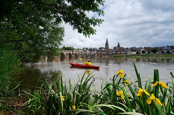 [FRANCE.BOURGOGNE 10777] 'Kayak approaching the Bridge of La Charité-sur-Loire.'  A kayaker approaches the medieval bridge in La Charité-sur-Loire. In former days the navigable arches were barred by chains and the ships passing the bridge had to pay toll. The spire of the Sainte-Croix-Notre-Dame towers above the medieval quarter of the town. Photo Mick Palarczyk.
