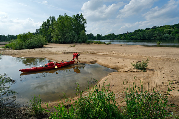"""[FRANCE.BOURGOGNE 10780] 'Kayaker near Tracy-sur-Loire.'  A kayaker is pulling his vessel on the sandy bank of a dead branch of the Loire, near Tracy-sur-Loire. Here the Loire meanders through the """"Reserve Naturelle Val de Loire"""", a stretch of 19 km downstream of La Charité-sur-Loire where the river has preserved much of its natural character. Photo Mick Palarczyk."""