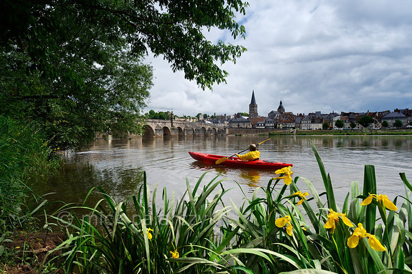 [FRANCE.BOURGOGNE 10776] 'Kayak approaching the Bridge of La Charité-sur-Loire.'  A kayaker approaches the medieval bridge in La Charité-sur-Loire. In former days the navigable arches were barred by chains and the ships passing the bridge had to pay toll. The spire of the Sainte-Croix-Notre-Dame towers above the medieval quarter of the town. Photo Mick Palarczyk.