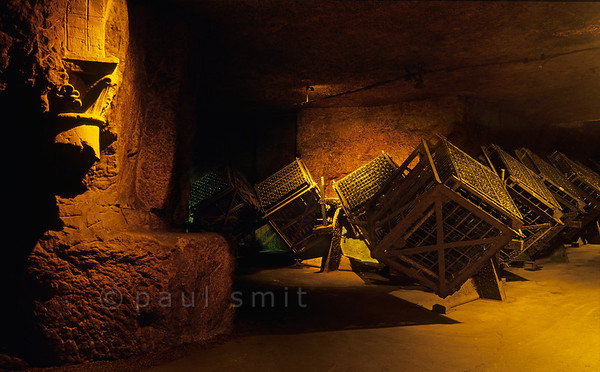 [FRANCE.LOIRE 10874] 'Méthode champenoise in Saumur.'  	These strange contraptions in the troglodytic wine cellars of Bouvet Ladubay in Saumur are used to rotate bottles with sparking wine on a daily basis. The wine ferments in the bottle ('méthode champenoise') and rotating them causes the yeast to sink to the top of the upturned bottle, where it is eventually removed. Sculptor Philippe Cormand has added architectonical elements to the cellars to lend them the atmosphere of a buried medieval cathedral. Photo Paul Smit.