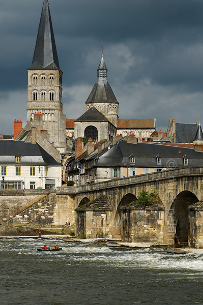 [FRANCE.BOURGOGNE 10774] 'Bridge of La Charité-sur-Loire.'  A canoe braves the turbulent waters downstream of the medieval bridge in La Charité-sur-Loire. In former days the navigable arches were barred by chains and the ships passing the bridge had to pay toll. The spire of the Sainte-Croix-Notre-Dame towers above the medieval quarter of the town. Photo Mick Palarczyk.