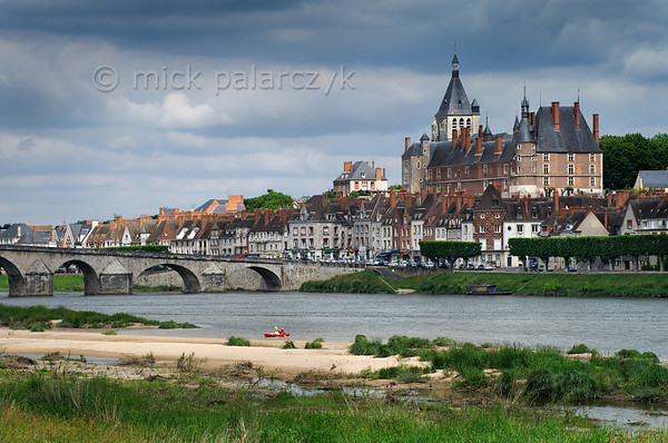 [FRANCE.LOIRE 10783] 'Kayaker on the Loire at Gien.'  	A kayaker approaches the sandy bank of the Loire at Gien, a town that is dominated by the brick-built Castle of Anne de Beaujeu (ca. 1500). The Loire bridge originally dates from the Middle Ages but was reconstructed in the 18th century. Photo Mick Palarczyk.