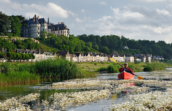 [FRANCE.LOIRE 10828] 'Chaumont's Castle seen from a paddler's perspective.'  The 15th century castle of Chaumont-sur-Loire looks down on a paddler navigating the loire between Blois and Amboise. Locally the river is covered by large patches of flowering River Water-crowfoot (Ranunculus fluitans; NL: Vlottende waterranonkel). Rooted in the riverbed, it produces strands of up to 6 meters in length, that are stretched out in the direction of the current. Photo Mick Palarczyk.