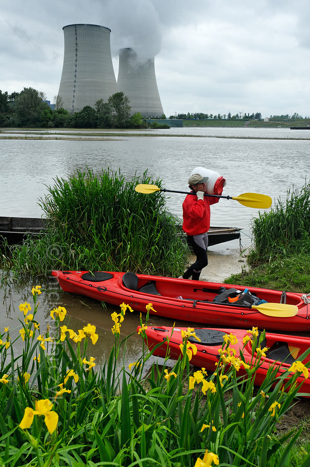 [FRANCE.BOURGOGNE 10782] 'Portage at Belleville power plant.'  Near the nuclear power plant at Belleville-sur-Loire the Loire tumbles down a weir and kayakers are obliged to make use of the portage. Yellow Irises soften up an industrial environment dominated by giant cooling towers. Photo Mick Palarczyk.