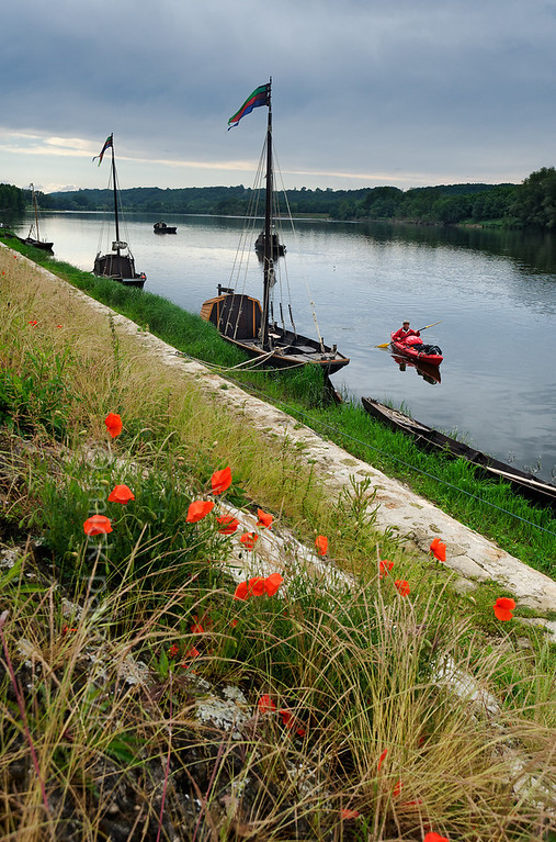[FRANCE.LOIRE 10846] 'Loire quay with poppies at Bréhémont.'  	The Loire quay at Bréhémont with its moored traditional flatboats ('chalands') is an interesting spot to investigate for kayakers. Photo Mick Palarczyk.