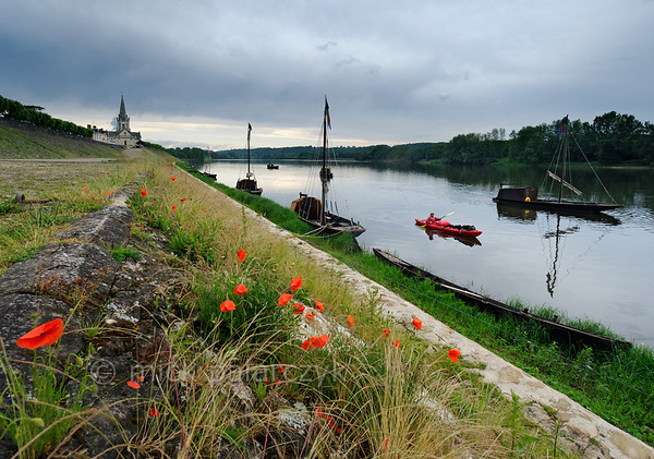[FRANCE.LOIRE 10848] 'Loire quay with poppies at Bréhémont.'  	The Loire quay at Bréhémont with its moored traditional flatboats ('chalands') is an interesting spot to investigate for kayakers. Photo Mick Palarczyk.