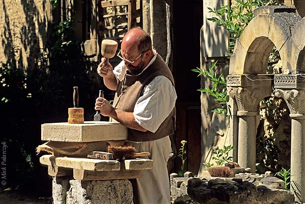 [FRANCE.RHONE 24.614 'Sculptor in St. Antoine-1.'  Sculptor Claude Chevènement prepares a block of stone in front of his workshop in St. Antoine-l'Abbaye. This medieval village, which has retained much of its original atmosphere, has become a favourite residence for artist sand artisans. Photo Mick Palarczyk.