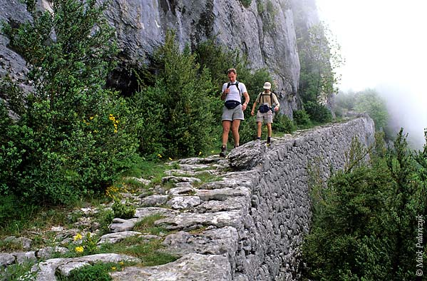 [FRANCE.ALPSNORTH 24.455] 'Hikers on mule track-2.'  South of Pont-en-Royans an ancient mule track leads up the perpendicular slope of the Grande Cournouse towards the Pas de l'Allier. Till the 19th century tracks like these were the only way to cross the Vercors in an east-west direction. They were mainly used by charcoal burners who worked high up in the woods. Photo Mick Palarczyk.