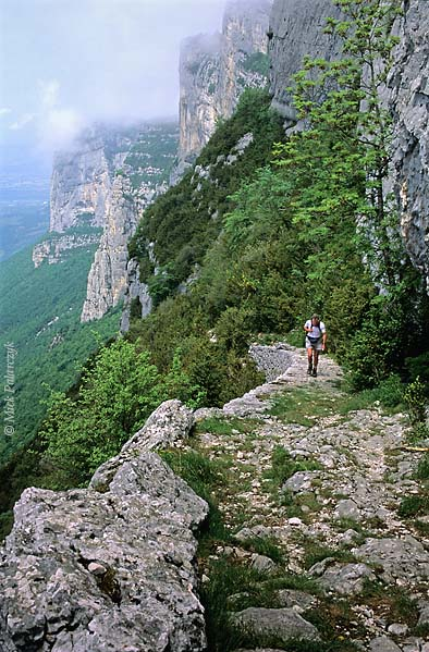 [FRANCE.ALPSNORTH 24.467] 'Hikers on mule track-5.'  South of Pont-en-Royans an ancient mule track leads up the perpendicular slope of the Grande Cournouse towards the Pas de l'Allier. Till the 19th century tracks like these were the only way to cross the Vercors in an east-west direction. They were mainly used by charcoal burners who worked high up in the woods. Photo Mick Palarczyk.