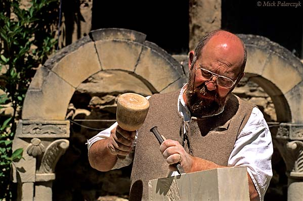 [FRANCE.RHONE 24.630 'Sculptor in St. Antoine-3.'  Sculptor Claude Chevènement prepares a block of stone in front of his workshop in St. Antoine-l'Abbaye. This medieval village, which has retained much of its original atmosphere, has become a favourite residence for artist sand artisans. Photo Mick Palarczyk.