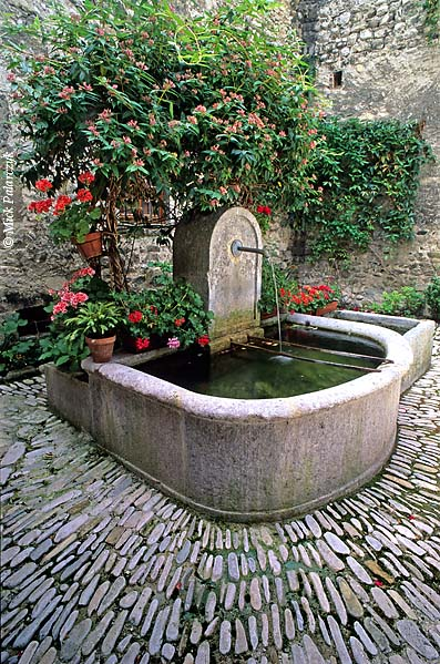 [FRANCE.ALPSSOUTH 24.372] 'Well in Châtillon.'  Honeysuckle and geraniums frame an old well on a square in Châtillon-en-Diois. Photo Mick Palarczyk.