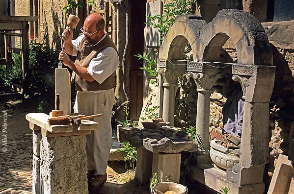 [FRANCE.RHONE 24.623 'Sculptor in St. Antoine-2.'  Sculptor Claude Chevènement prepares a block of stone in front of his workshop in St. Antoine-l'Abbaye. This medieval village, which has retained much of its original atmosphere, has become a favourite residence for artist sand artisans. Photo Mick Palarczyk.