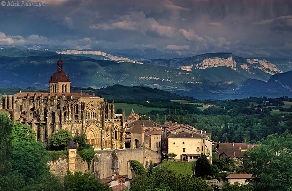 [FRANCE.RHONE 24.589 'Abbey church and cliffs.'  Behind the Gothic abbey church of St. Antoine-l'Abbaye, the vertical cliffs at the western edge of the Vercors massif catch the evening sunlight. Photo Mick Palarczyk.