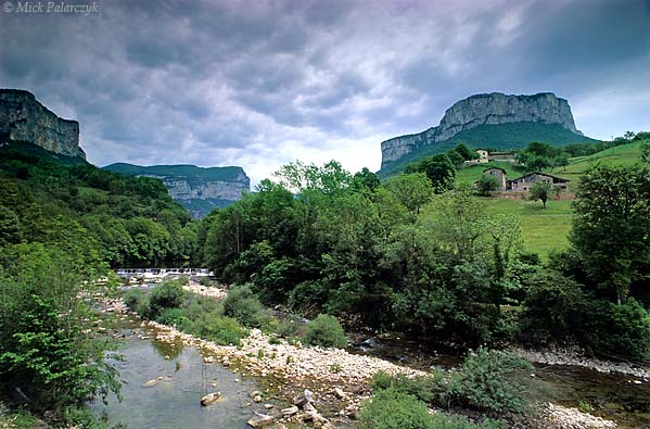 [FRANCE.ALPSNORTH 24.431] 'Grande Cournouse.'  From the Gorges de la Bourne near Choranche there is an imposing view of the steep limestone walls surrounding the Grande Cournouse (right). The gorges of the Vercors have been cut by glaciers and melt water during the Ice Age. Photo Mick Palarczyk.