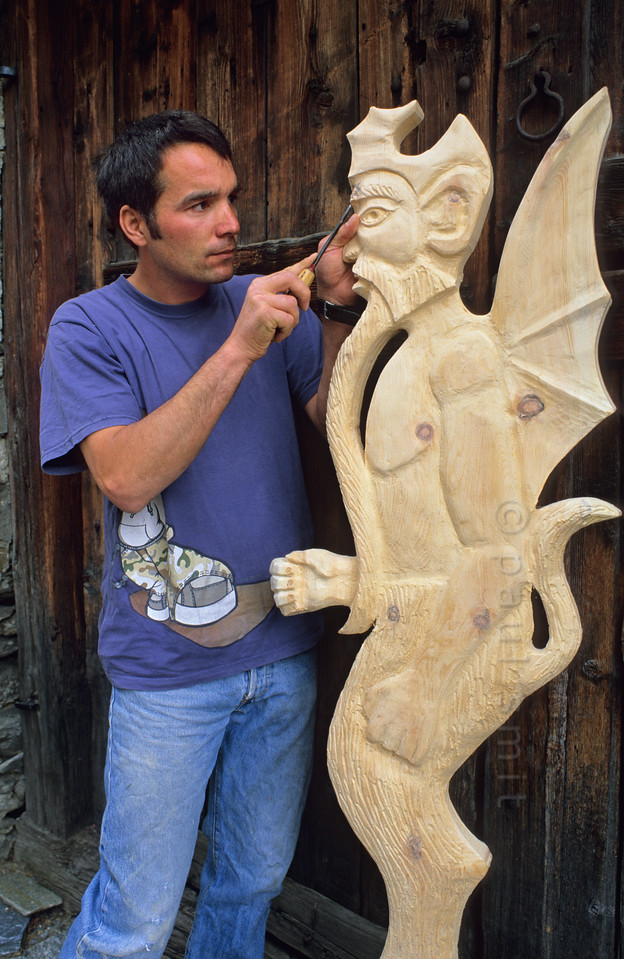 """[FRANCE.ALPSNORTH 10955] 'Sculptor of the devil.'  Already for centuries Bessans is a centre of religious wood carving. But only from the 19th century on the main subject became the devil. It's because a greedy pastor didn't fulfill his promice to offer the villagers a free meal once a year. So a local woodcutter sculpted a devil and, one night, put it in the window of the pastor. Ofcourse the pastor realized who had played a trick on him and put the devil in the window of the culprit. For a month the wood carving went back and forth, until the artist left it in his own window. By that time Bessans had become known for its devil and the new wood carving orders flowed in. Today this tradition is continued by sculptor Fabrice Personnaz, who has his atelier """"Le Chapoteur"""" in Bessans. Photo Paul Smit."""