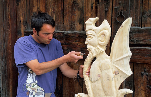 """[FRANCE.ALPSNORTH 10956] 'Sculptor of the devil.'  Already for centuries Bessans is a centre of religious wood carving. But only from the 19th century on the main subject became the devil. It's because a greedy pastor didn't fulfill his promice to offer the villagers a free meal once a year. So a local woodcutter sculpted a devil and, one night, put it in the window of the pastor. Ofcourse the pastor realized who had played a trick on him and put the devil in the window of the culprit. For a month the wood carving went back and forth, until the artist left it in his own window. By that time Bessans had become known for its devil and the new wood carving orders flowed in. Today this tradition is continued by sculptor Fabrice Personnaz, who has his atelier """"Le Chapoteur"""" in Bessans. Photo Paul Smit."""