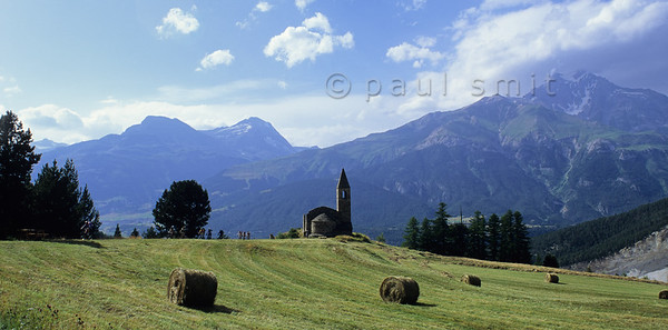 [FRANCE.ALPSNORTH 11000] 'Oldest church of Savoy.'  Mountainbikers ride past the ruins of the 11th century church Saint Pierre-d'Extravache near Bramans, the oldest church in Savoie. It looks out over the Vanoise national park to the north, with the Dent Parachée (3687 m) at right. Photo Paul Smit.