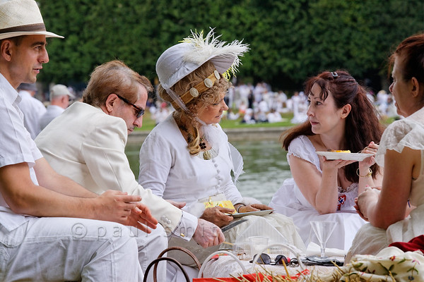 """[FRANCE.ILEDEFRANCE 11034] 'White Picnic of Versailles.'  On Bastille Day, the 14th of July, a wonderful """"Déjeuner sur l'Herbe"""" is organized in the gardens of the Palace of Versailles. Thousands of people come together with their picnic baskets and have a festive meal on the banks of the Grand Canal. In English it is known as the Picnic of Versailles or the White Picnic (""""pique-nique en blanc""""), since white is the dress code. Many people enjoy to dress up for the occasion and some look at impressionist paintings like the """"Luncheon of the Boating Party"""" by Renoir for inspiration. However, the lady with the hat goes even further back in time and reminds us of the days of Marie-Antoinette. Photo Paul Smit."""