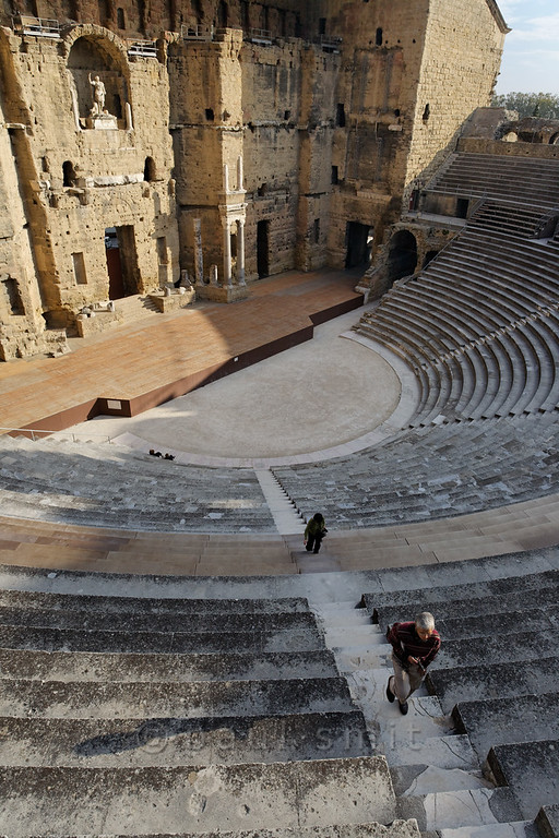 [FRANCE.PROVENCE 10885] 'Roman theatre in Orange.'  The Roman theatre in the town of Orange has one of the only two remaining back walls (sceanea frons) which are still standing. These back walls were essential for good acoustics. Productions staged here ranged from Greek tragedies, musical performances, and acrobatics to political talks.  When christianity became the state religion under Emperor Constantine the Roman theatres were closed down and this may have been a severe blow to the integrity of the Empire. The theatre provided a sense of Roman identity for all its visitors throughout the ethnically divers Empire. Closing down the theatres may have been as shocking as taking television away from the modern world.  The theatre in Orange was built between AD 10 and 25 (during the rule of Emperor Augustus) and is on the World Heritage List of the UNESCO. Photo Paul Smit.