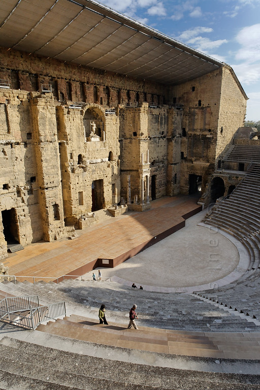 [FRANCE.PROVENCE 10884] 'Roman theatre in Orange.'  The Roman theatre in the town of Orange has one of the only two remaining back walls (sceanea frons) which are still standing. These back walls were essential for good acoustics. Productions staged here ranged from Greek tragedies, musical performances, and acrobatics to political talks.  When christianity became the state religion under Emperor Constantine the Roman theatres were closed down and this may have been a severe blow to the integrity of the Empire. The theatre provided a sense of Roman identity for all its visitors throughout the ethnically divers Empire. Closing down the theatres may have been as shocking as taking television away from the modern world.  The theatre in Orange was built between AD 10 and 25 (during the rule of Emperor Augustus) and is on the World Heritage List of the UNESCO. Photo Paul Smit.